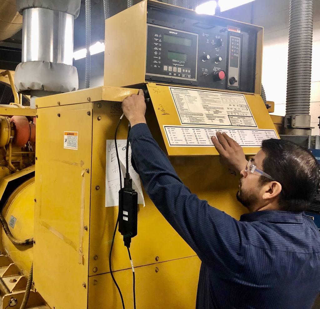 Technician setting up remote generator monitoring