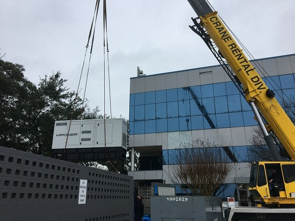 Generator being lowered onto concrete pad